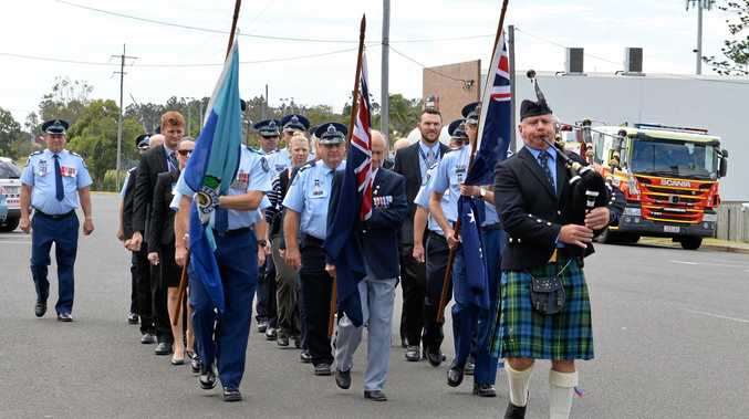 MARCHING ON: Police march towards the Uniting Church for today's service.