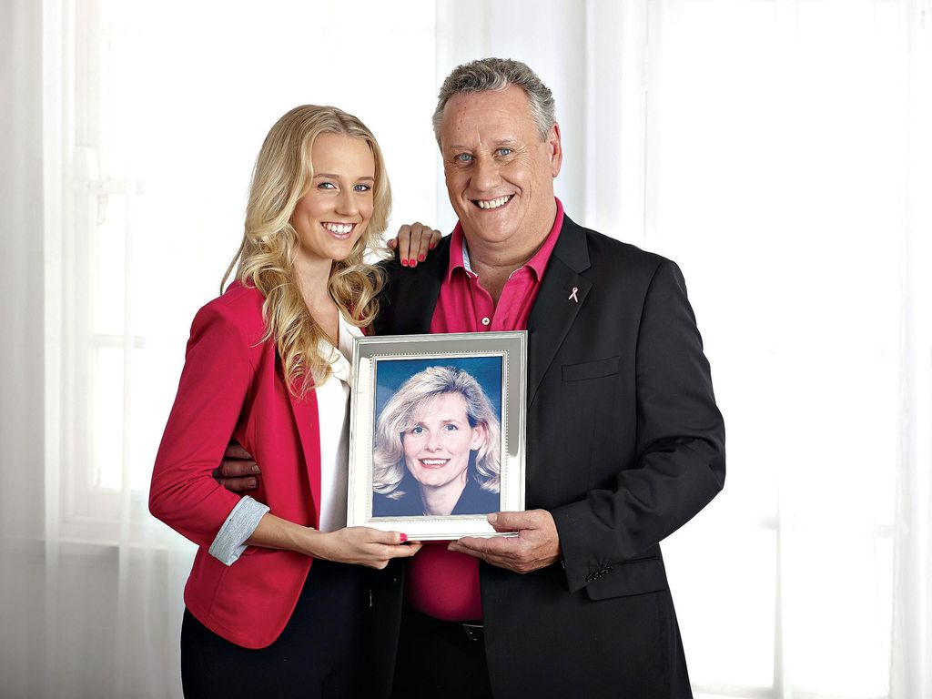 Laura and her father Mark hold a photo of Anni, who died in 2007 following a battle with breast cancer.