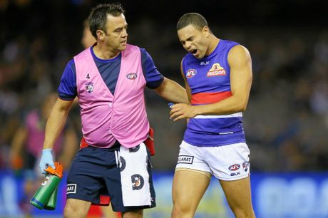 MELBOURNE, AUSTRALIA - APRIL 16:  Jake Stringer consoles Jason Johannisen comes off after he injures his hamstring when kicking the ball for a goal during AFL Round 4 match between the Carlton Blues and the Western Bulldogs at Etihad Stadium on April 16, 2016 in Melbourne, Australia.  (Photo by Michael Dodge/Getty Images)