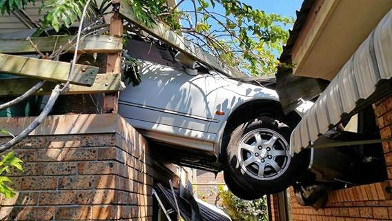 THROUGH THE ROOF: Police are investigating after an elderly woman crashed her car.