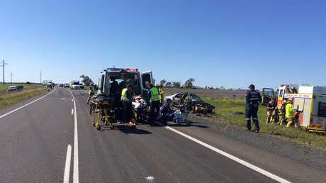 Queensland Ambulance paramedics and RACQ LifeFlight's critical care doctor treat a Dalby man, 18, at the scene of a three-vehicle crash on the Warrego Hwy east of Dalby on Sunday.