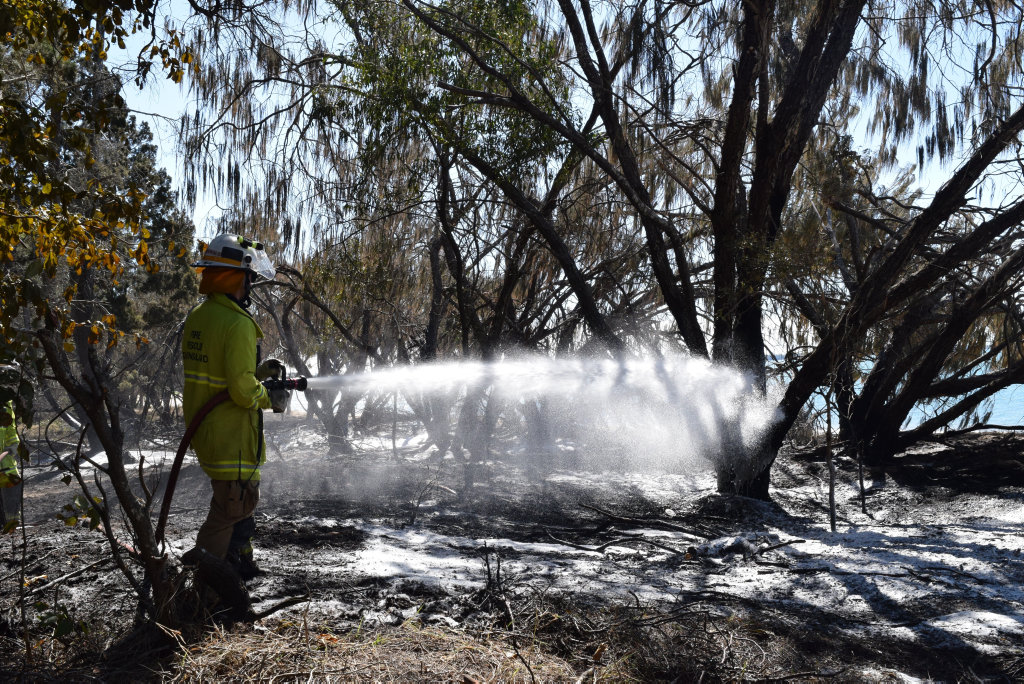 SCRUB FIRE: An officer from the Torquay Fire Station hoses down the foreshore behind Torquay beach.