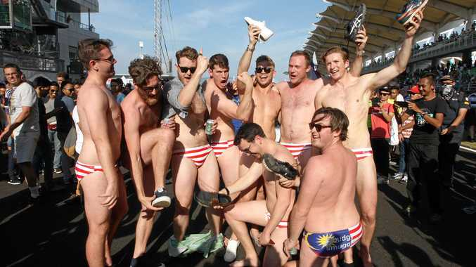 In this Sunday, Oct. 2, photo, Australian men celebrate in Budgy Smuggler-brand swimsuits decorated with the Malaysian flag at the conclusion of the Malaysian Formula One Grand Prix in Sepang, Malaysia.