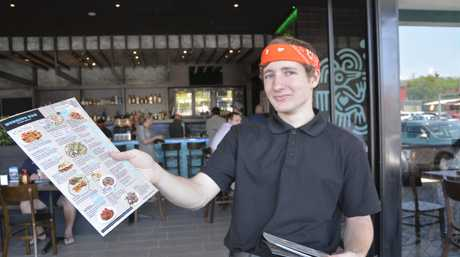 The Burrito Bar staff member Aaron Evans hands out menus to keen foodies.