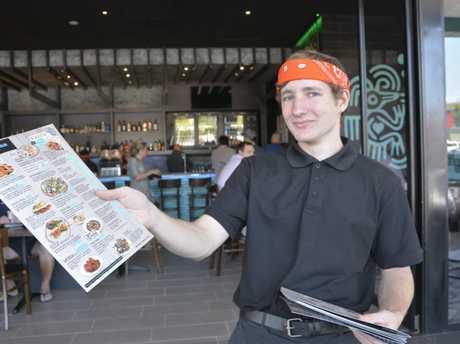 The Burrito Bar staff member Aaron Evans hands out menus to keen foodies.