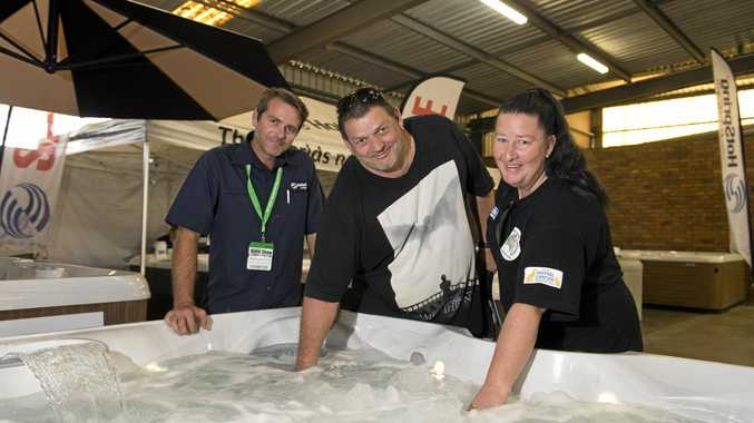 Lex Grive (left) shows Brett Torcetti and Tina Torcetti the range of spas on offer at the Toowoomba Spring Home Show.