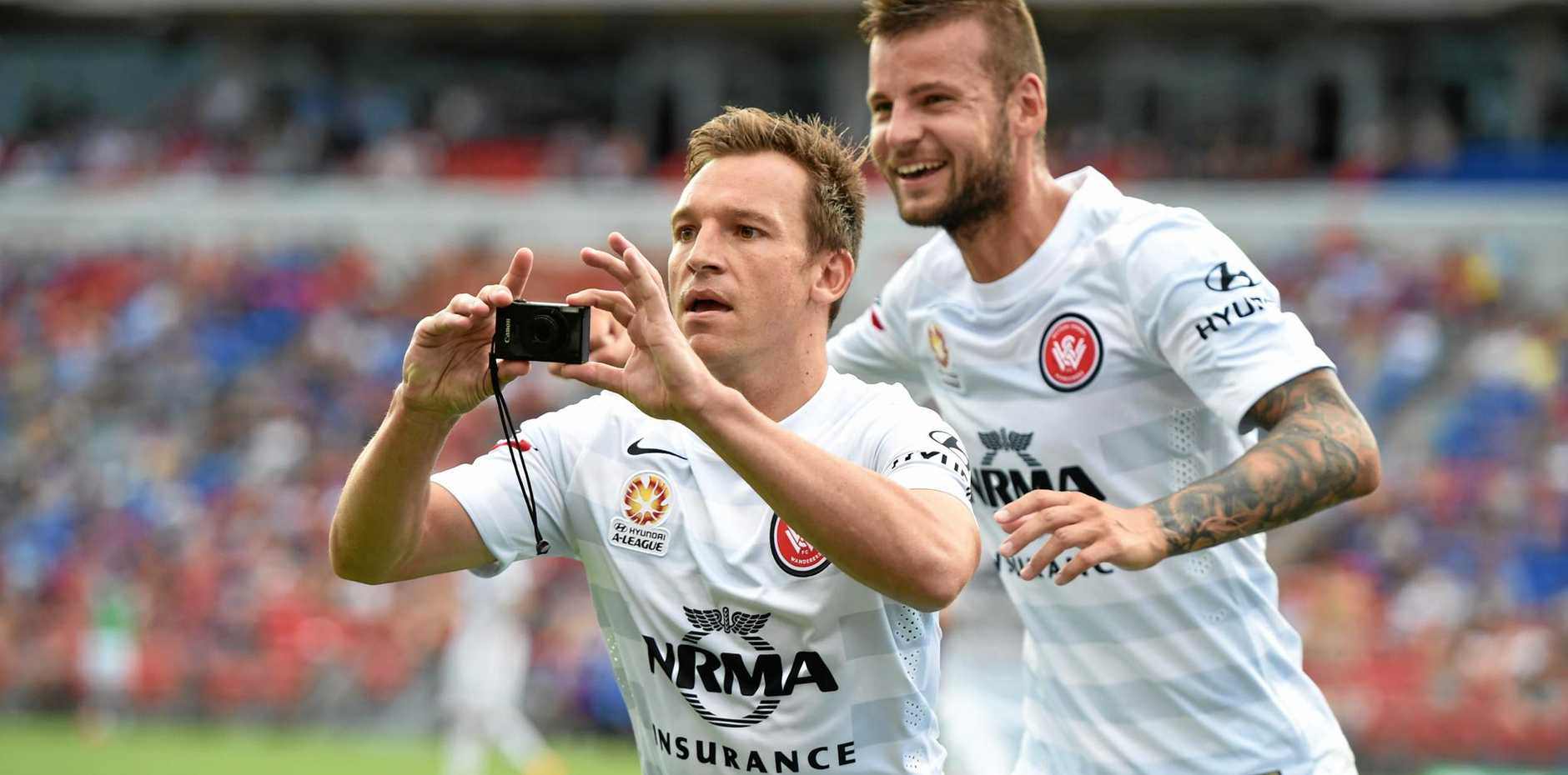 Western Sydney forward Brendon Santalab takes a photo of Wanderers supporters after scoring last season.