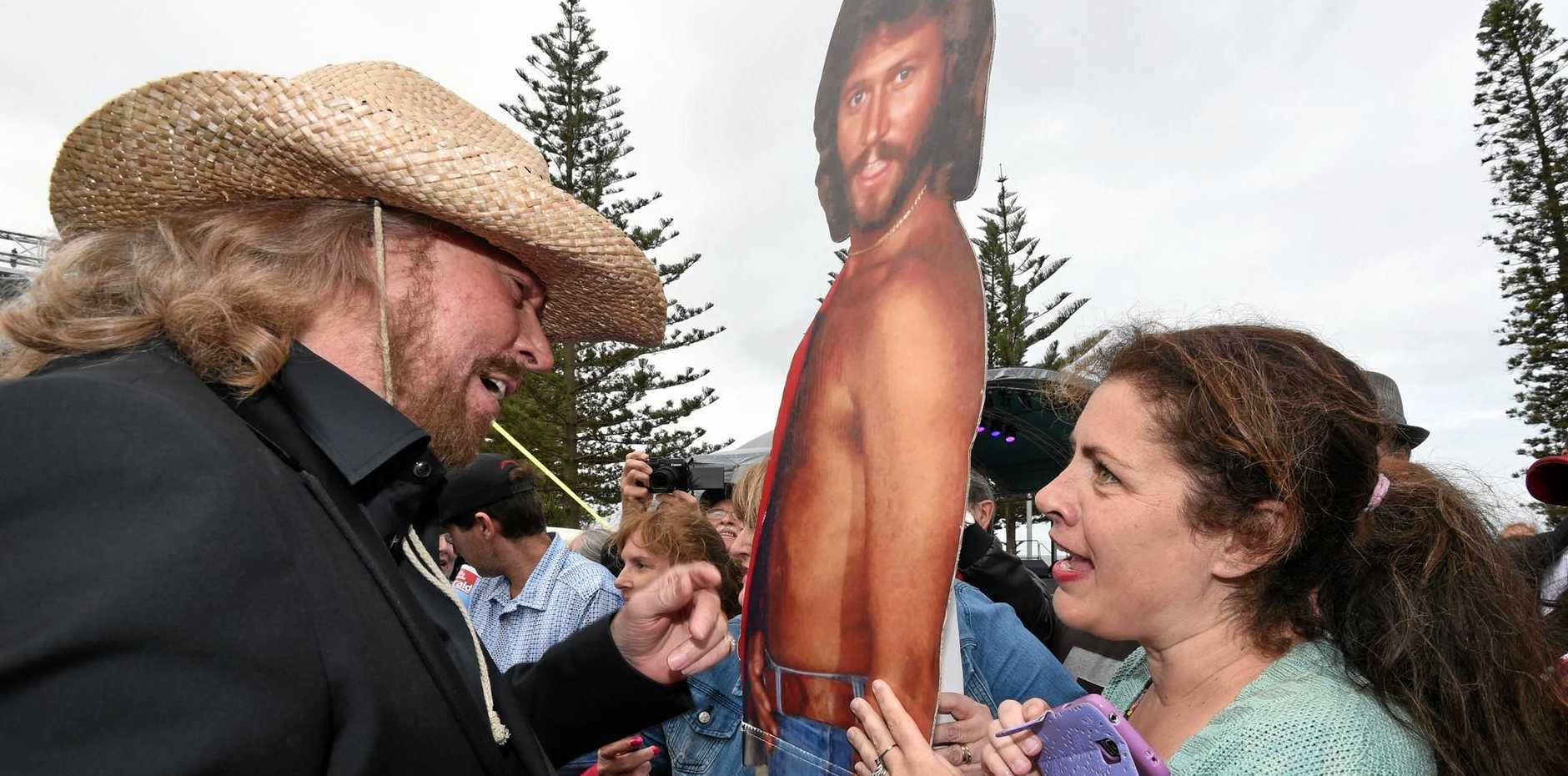 FANS: Barry Gibb talks to a fan next to a cardboard cutout of his young self.