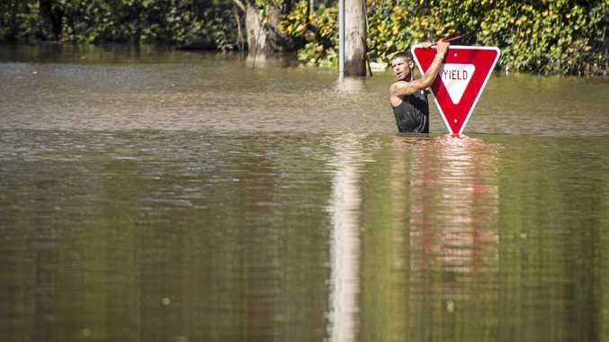 A man holds on to a sign after trying to swim out to help a stranded truck driver in Hope Mills, North Carolina