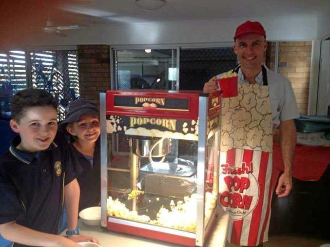 Hamish Malone, Austin Pronger, Tim Malone warm up the popcorn machine ahead of the St. Patrick's Spring Fair.