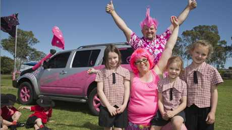 THINKING PINK: Scott and Bec Waters had help from Sacred Heart Primary School students (from left) Brooke Whittaker, Izabella Waters and Amber Harmsen when they decorated their car for a fundraising rally.