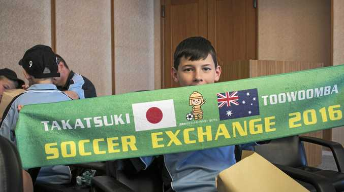 Toowoomba team member Sam Fraser displays a cloth banner given to members to mark the 2016 Soccer Exchange.