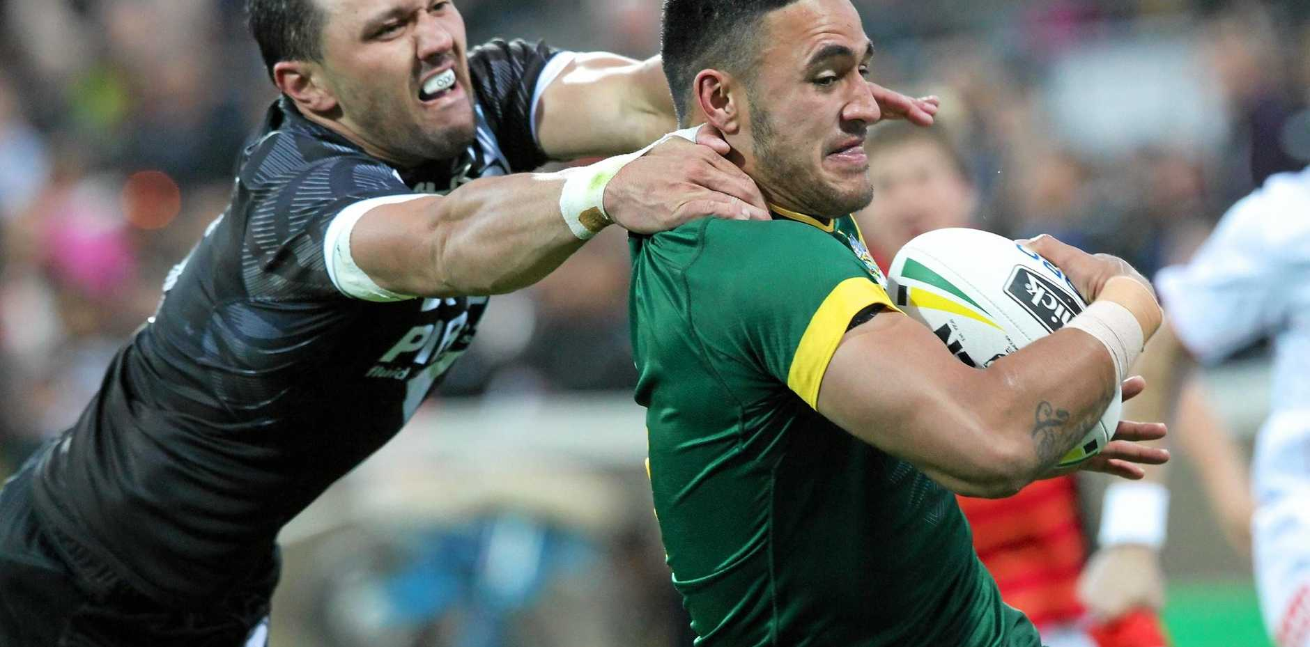 Valentine Holmes of the Kangaroos evades a tackle to score a try against the Kiwis.