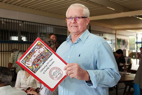 Former Urangan Point State School principal Neil Collins buys a centenary book.