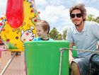 Aaron Tewes takes his grandson Chevy Tewes, 4, on a teacup ride at the centenary.
