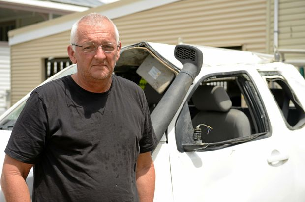 Wayne Sichter with his wrecked car that was stolen from his home.