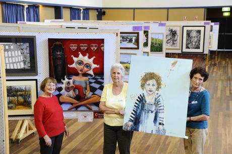 Grafton Art Club's Shirley Passmore, Gwen Green and Mary McEwan with the Jacaranda Art Exhibition Bendigo Bank Open Winner - Chris Hazell's Reflection and portraiture winner Julie Hutchings' Kokoda Rose. Photo JoJo Newby / The Daily Examiner