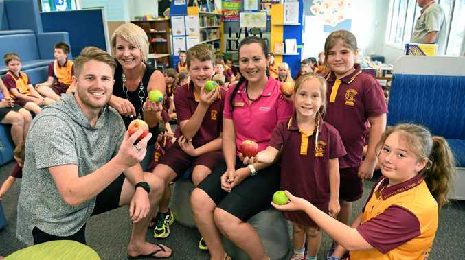 SPOILT FOR CHOICE: Bundaberg Central State School teacher Kym Childs accepts apples from Hitz 939's Bryce and Trace, Harmon Josefski, Mia Russell, Amelia Petersen and Lauren Rhodes.