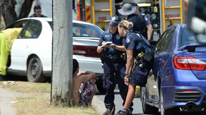 Police talk to a person at the scene of a car crash into a tree on Farm Street Rockhampton.