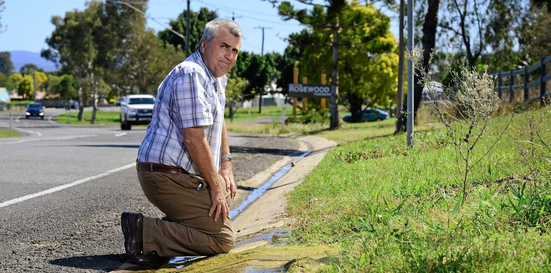 ROAD DAMAGE: Cr David Pahlke watches on as water from a nearby spring drains onto Karrabin Rosewood Rd at Rosewood. He is worried the long-term leak will cause damage to the well-used road.