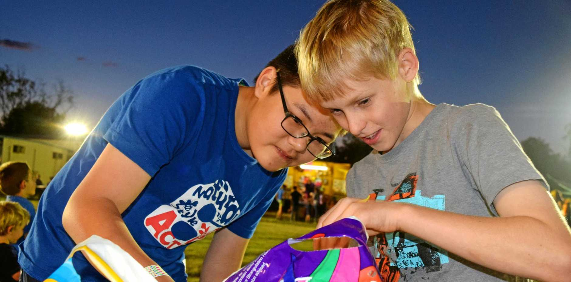 SPRING FUN: Bo Hao and Ben Hall examine the showbags at St John's Moonlight Fair in 2015.