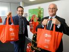 GOOD CAUSE: Wesley Mission representative Mike Jeffrey and Queenslander Credit Union CEO John Weier prepare for the Red Bag Appeal.