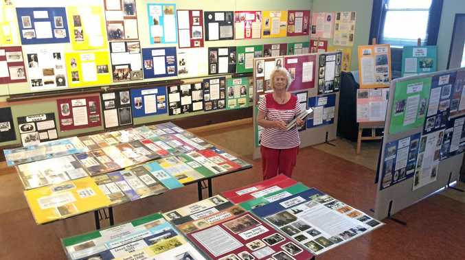 President of the Mackay Family History Society Carolan Hill surrounded by posters dedicated to Mackay's early settlers.