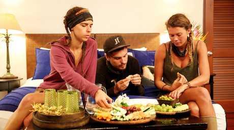 Kristie, Matt and Flick enjoy the fruits of a reward challenge win in a scene from Australian Survivor.