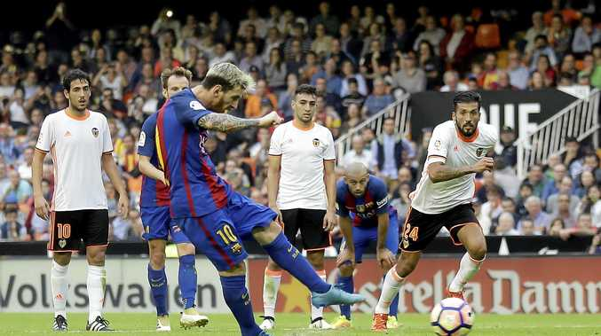 Barcelona's Lionel Messi kicks for the ball to score a penalty during the La Liga soccer match against Valencia at the Mestalla stadium in Valencia.