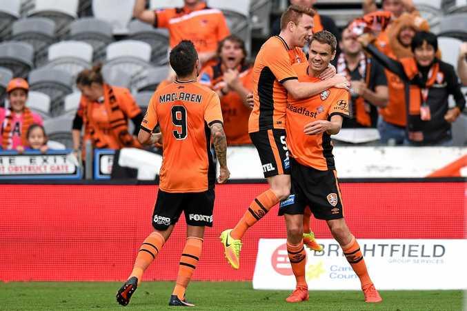 Thomas Kristensen of the Roar (right) celebrates with teammates after scoring against the Mariners.