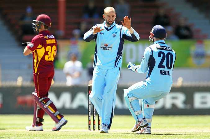 Nathan Lyon of the Blues celebrates with teammate Peter Nevill after claiming the wicket of Ben Cutting of the Bulls.