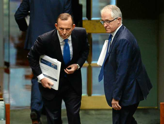**FILE** A  Monday, Sept. 14, 2015 file image of Australian Prime Minister Tony Abbott (left) and Federal Minister for Communications Malcolm Turnbull at the conclusion of Question Time in the House of Representatives at Parliament House, in Canberra. Following weeks of speculation, former prime minister Tony Abbott has confirmed he will recontest the federal seat of Warringah at the next election. (AAP Image/Sam Mooy) NO ARCHIVING