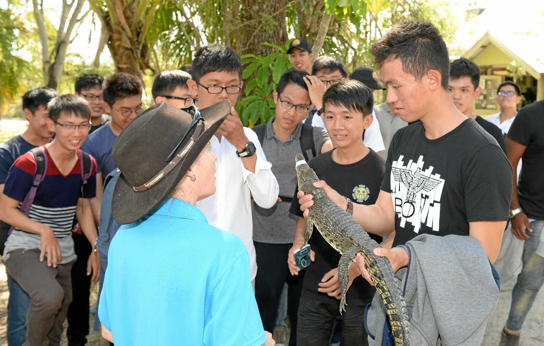 One of the Singaporean soliders in Rockhamtpon for Exercise Wallaby holds a crocodile at Koorana Crocodile Farm on the Capricorn Coast.