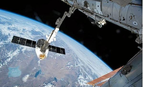 In this picture taken from NASA's International Space Station from April 2015, the SpaceX Dragon is captured with the 57.7-foot-long Canadarm2 robotic arm before its installation to the Harmony module.