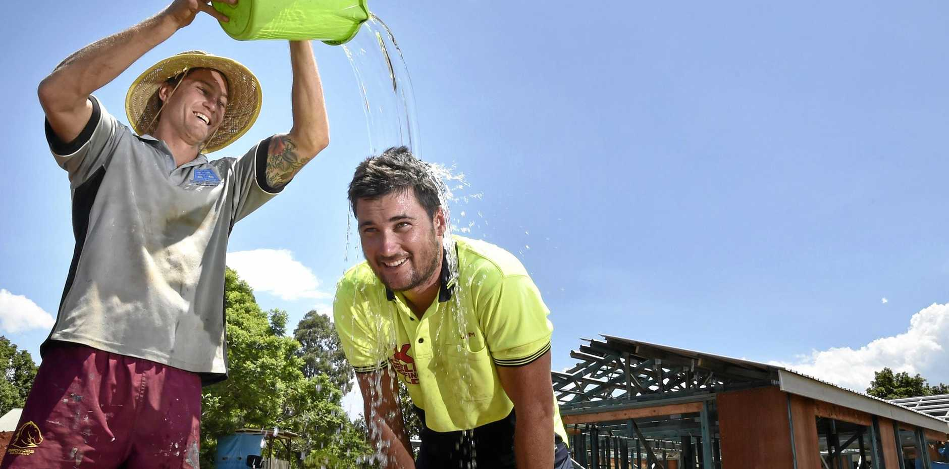 HEAT WAVE: Everyone has their own unique way of coping with above average summer heat,. Tradies Matthew Bryant (left) and Sam Finn found a simple, quick method to cool down.