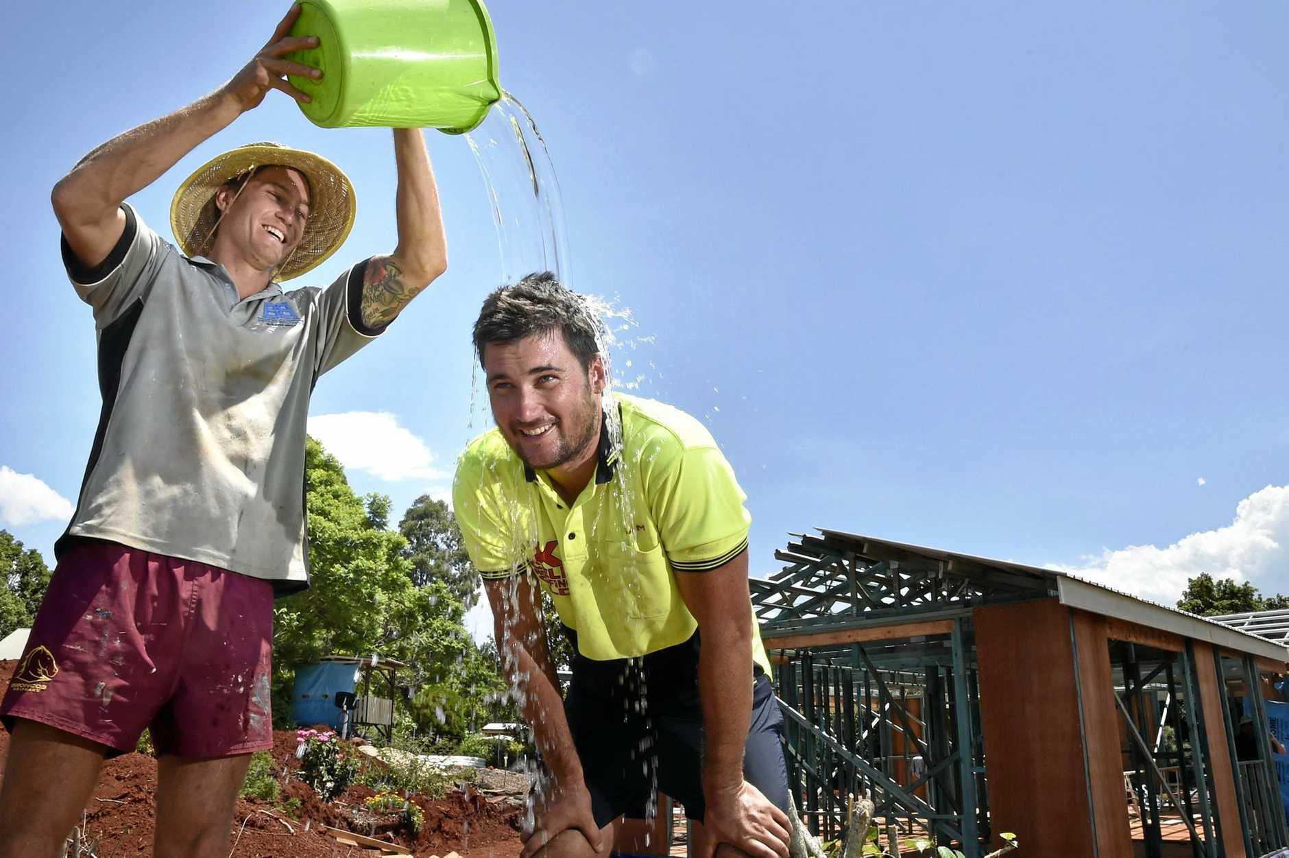 HEAT WAVE: Everyone has their own unique way of coping with above average summer heat,. Tradies Matthew Bryant (left) and Sam Finn found a simple, quick method to cool down. Photo Bev Lacey / The Chronicle
