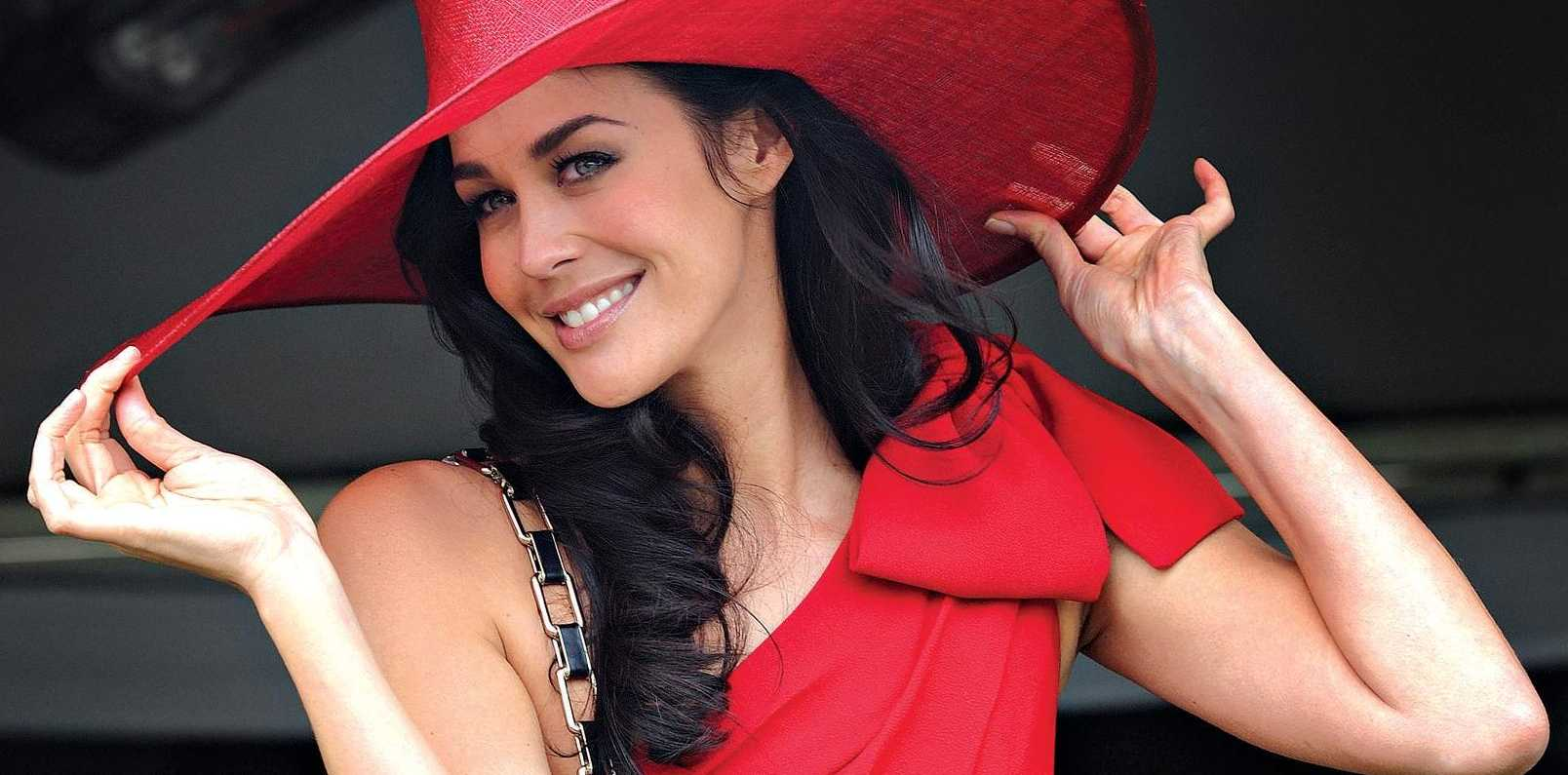 Model Megan Gale wears a red dress and matching hat at the Caulfield Cup race day, at Caulfield race track, in Melbourne, in 2009.