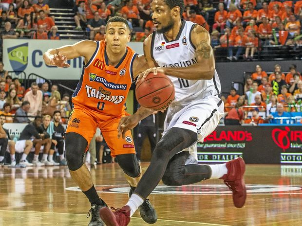 Melbourne United's Ramone Moore takes on Cairns' Travis Trice (left).