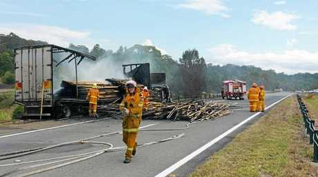 Emergency services personnel at the scene of the two-truck accident that closed the Pacific Highway at Chinderah.