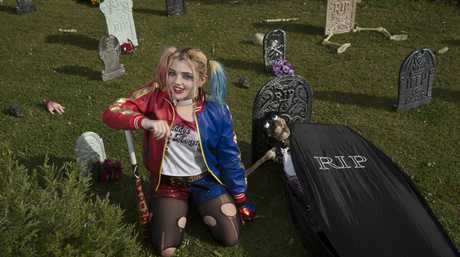 Mikaela Berry gets into the spirit of Halloween in the front yard of her Centenary Heights home, Thursday, October 27, 2016.