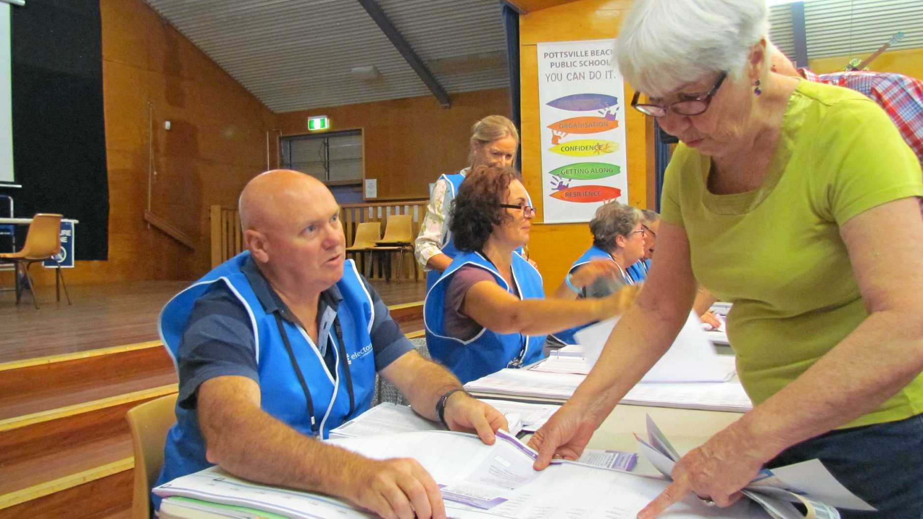 Pottsville resident Shirley FitzGerald gets her ballot paper from electoral commission worker Richard Johnston at the Pottsville Beach Public School booth
