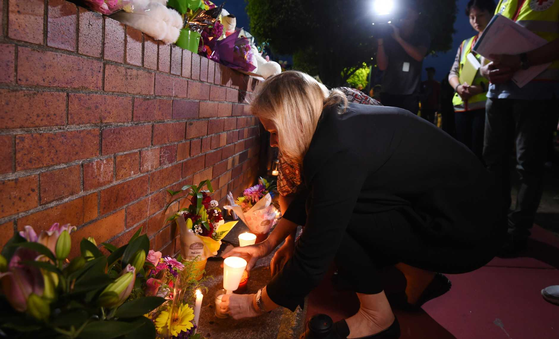 Ardent Leisure CEO Deborah Thomas places a candle during a vigil outside Dreamworld on Friday, Oct 28, 2016. Ms Thomas, along with Dreamworld CEO Craig Donaldson, has paid tribute to four people who were killed in an accident on a ride on Tuesday. Picture: AAP