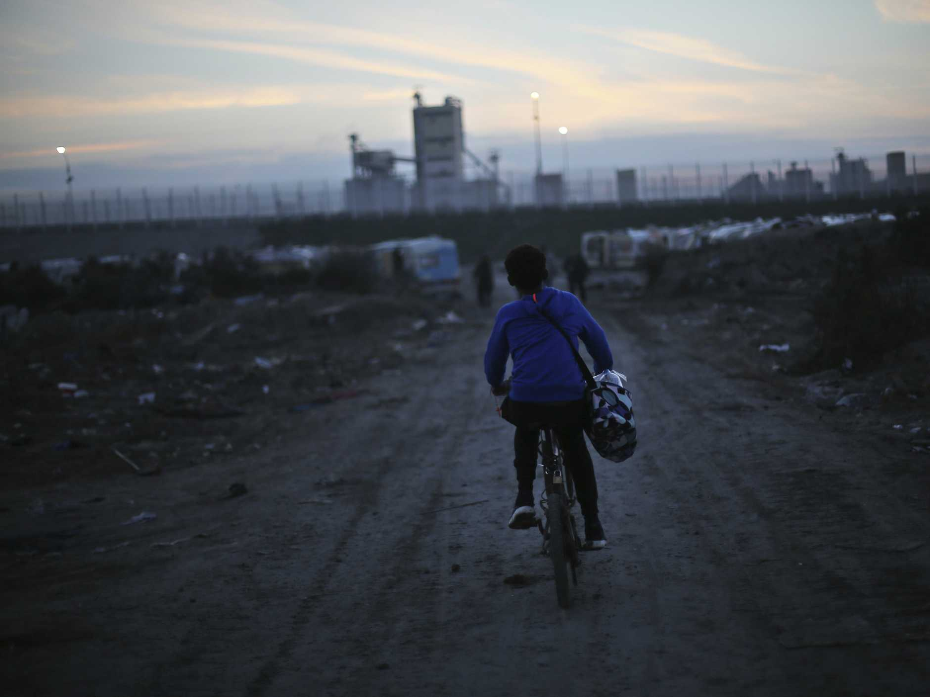 A boy rides a bicycle on the remains of the makeshift migrant camp known as