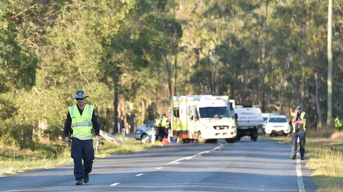Police crash investigators inspect Old Toogoom Rd at the scene of a fatal accident.