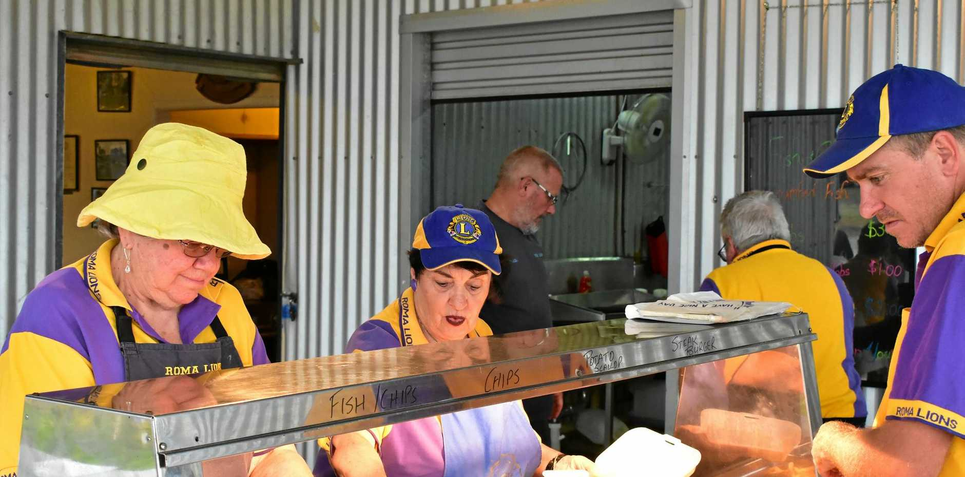 Roma Lions Club members serve up hot chips.
