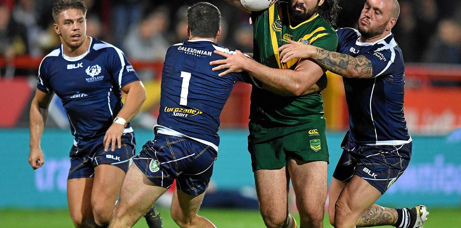 Australia's Aaron Woods is tackled by Scotland's Lachlan Coote and Dale Ferguson during their Four Nations match in Hull.
