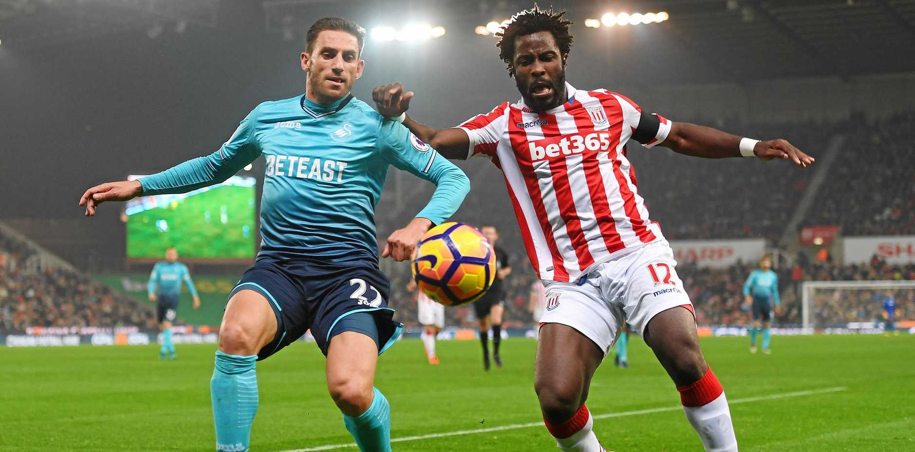 Angel Rangel of Swansea City and Wifried Bony of Stoke City battle for the ball.