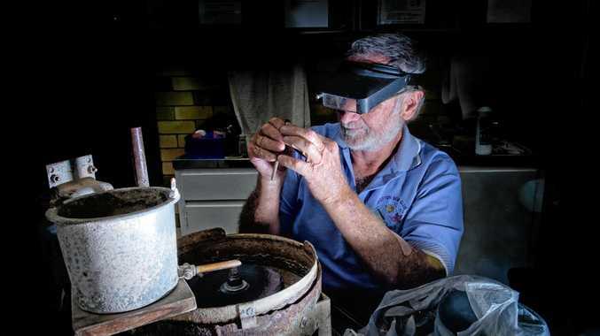 Derek Higgins works on polishing some opals at the Jacaranda Gem Club display.