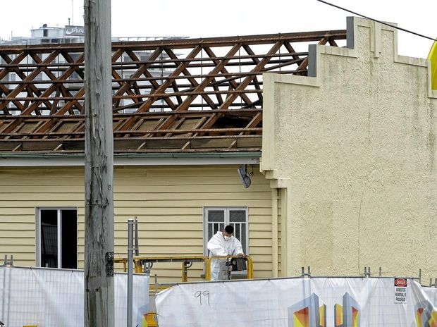 Workers remove the roof from the old firemans hall in Limestone Street in preparation for its demolition to extend the McDonald's carpark.
