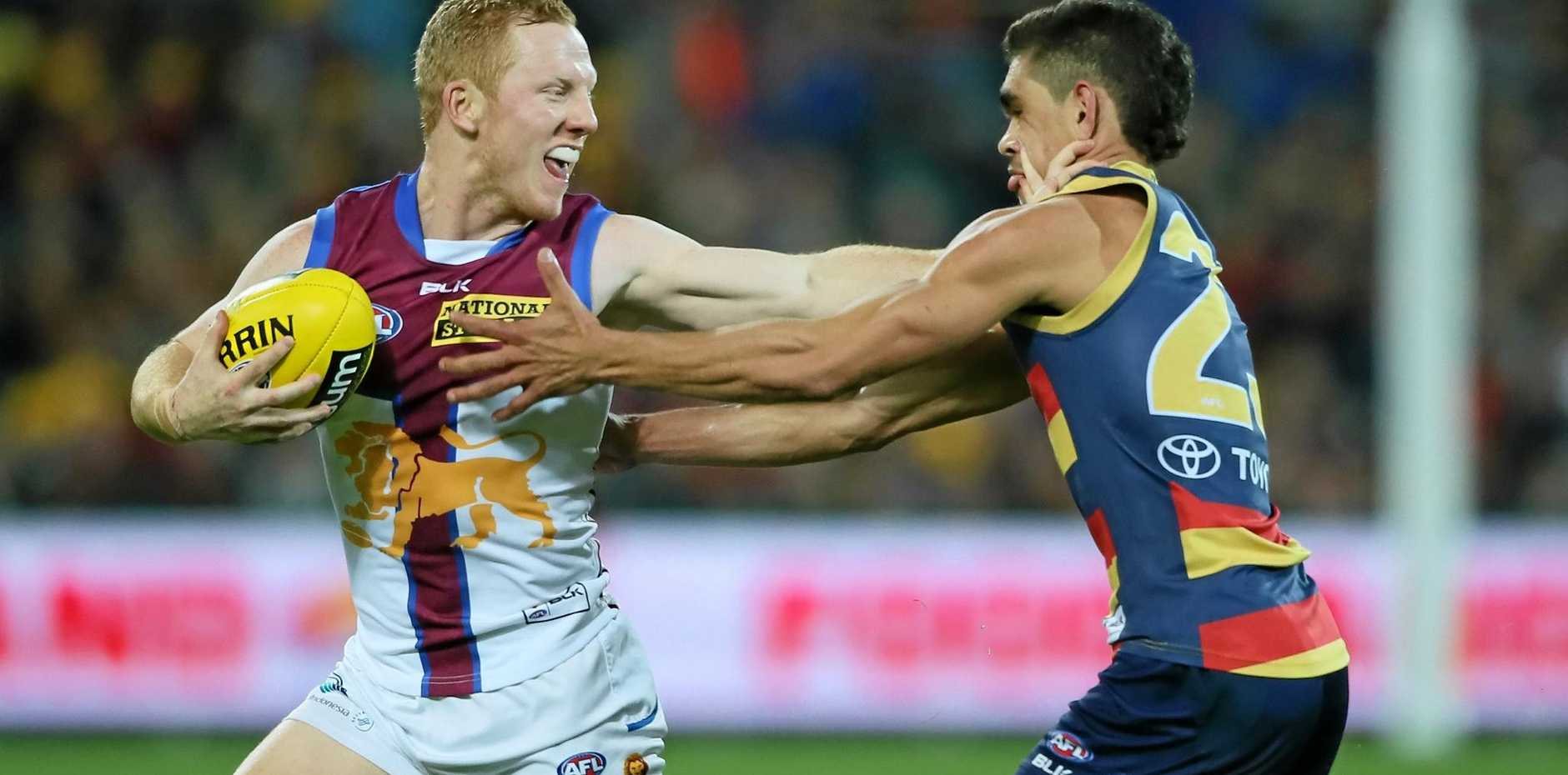 Josh Green of the Lions palms away attack from Charlie Cameron of the Crows.